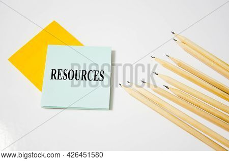 Word Written On A Yellow Piece Of Paper And White Background With Pencils Lying Next To It. Text