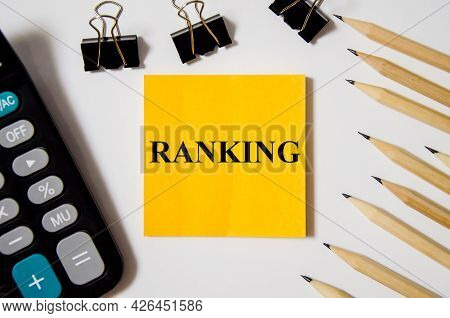 Ranking Word Is Written On A Yellow Piece Of Paper On A White Background Near A Calculator And A Pen