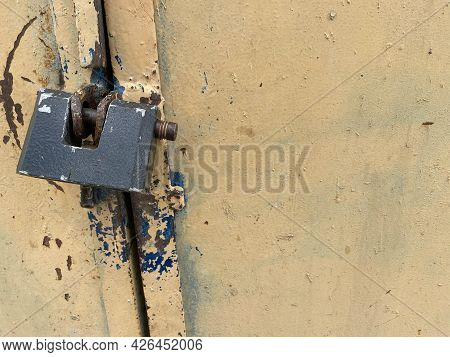 Yellow Old Scratched Padlock Metal Sheet, Iron Rusty Surface With Peeling Paint. The Background. Tex