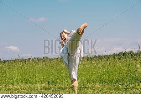 Teenage Girl Practicing Karate Kata Outdoors, Performs The Yoko Geri Kick With Kiai