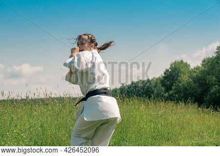 Teenage Girl Practicing Karate Kata Outdoors, Prepares To Uro Mawashi Geri (hook Kick)