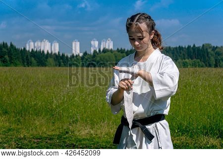 Teenage Girl In A Kimono Wrapping A Wrist Wrap Around Her Hand Before Starting Outdoor Karate Traini