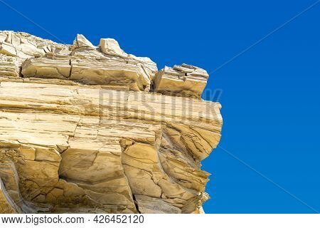 Fragment Of A Layered Limestone Rock Against A Blue Sky