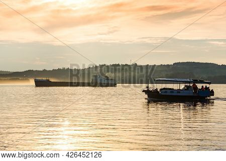 Passenger Boat And A Cargo Barge Float Down A Wide River In The Evening Light