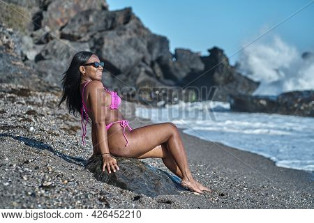 Young African American Woman Sitting, Sunbathing On The Shore Of The Beach