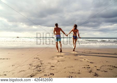Happy Couple Running On The Beach, Having Fun On Romantic Honeymoon Vacation