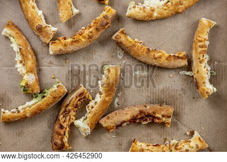 Pizza Crusts In A Greasy Box On A Home Table. Leftover Pieces Of Pizza. Bread Crumbs, Grease Stains