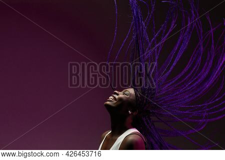 Minimal Portrait Of African-american Woman Dancing Against Purple Background With Purple Braids In A