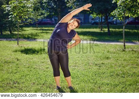 Fat European Woman Is Doing Standing Side Bends Exercise On Lawn In Park.