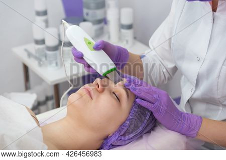 Beauty Salon. The Cosmetologist Makes A Water Peeling Procedure For The Client. Side View. The Conce