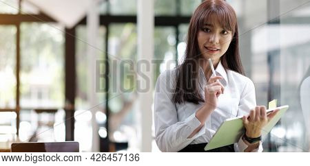 An Elegant Businesswoman Using A Tablet In The Back Of Her Office Is Standing Looking At The Camera.