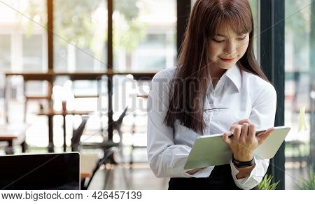 Young Adult  Business Lady In White Holding Digital Tablet  In Hands And Looking At Digital Tablet .