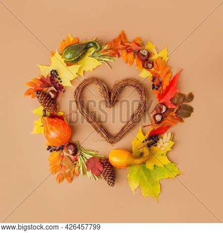 Autumn Heart Wreath From Dry Colored Leaves, Cones, Pumpkins, Squash, Black Berries On Beige Backgro
