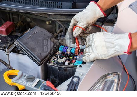 Auto Mechanic Working On Car Engine Checking Relay And Fuse In Mechanics Garage, Repair And Maintena