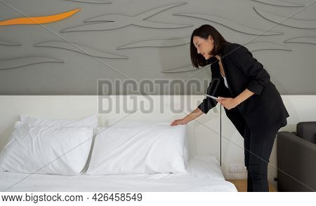 Asian Businesswoman In Black Suit Standing With Tablet Computer In Her Hand. The Hotel Manager Verif