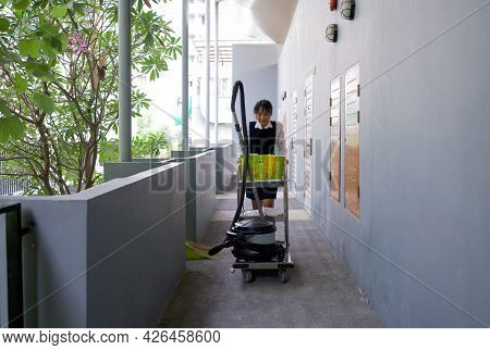 Asian Hotel Maid In Blue Uniform Push Housekeeping Cart On The Corridor In Front Of The Hotel Room.