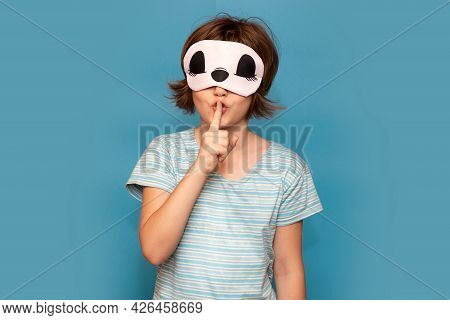 Cute Little Girl Wearing Sleep Mask Over Blue Isolated Background Ask To Be Quiet With Finger On Lip