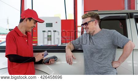 Gas Station Worker In Red Uniform Stand Smiling, Swipe Mockup Credit Card Via Payment Terminal. Cauc