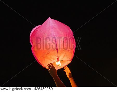 Hands Release A Paper Flashlight Into The Night Sky. Inside The Lantern, The Fire Burns Red. A Beaut