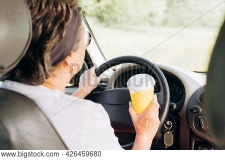 Mature Woman Driver Driving A Car And Holding A Disposable Cup Of Coffee On The Steering Wheel, Rear