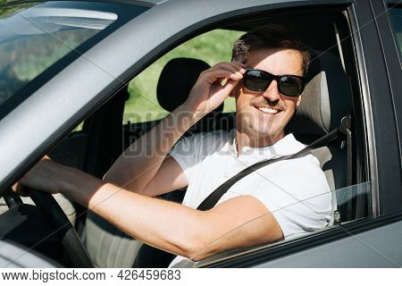 Portrait Of A Joyful Man In Glasses Driving A Car And Looking Out The Open Window. Smiling Handsome