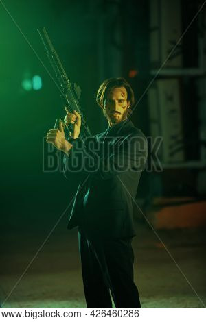 The criminal world in the big city. Courageous man with automatic gun in an industrial zone at night. Special agent.