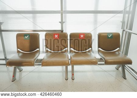 Empty Beige Seat Alignment In A Waiting Room With Symbol On Seat For The Social Distancing During Th