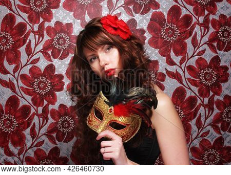 Young brunette woman with long curly hair with masquerade mask. Ready for party.
