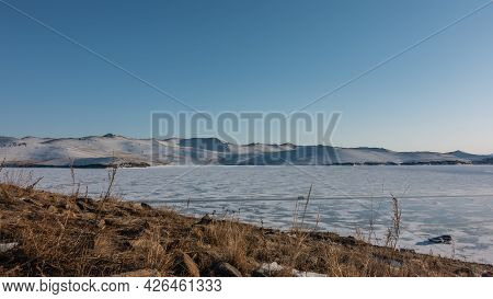 Winter Siberian Landscape. Snow Patterns On The Frozen Lake. Cars Are Standing On Ice. Dry Grass On