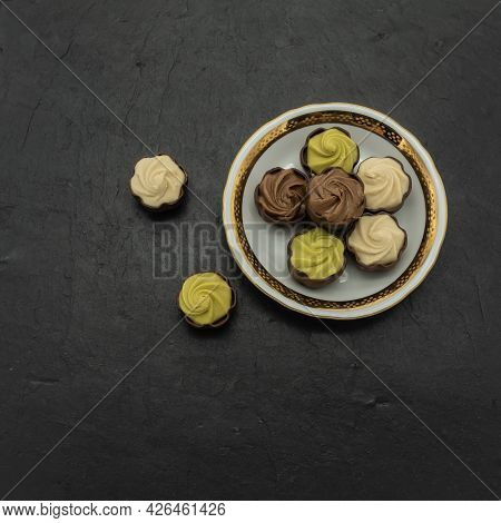 Chocolate Candies With Praline Stuffing, Pistachio, Creamy On A Porcelain Saucer With A Gold Rim. Tw