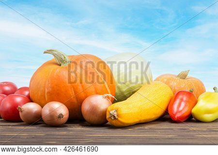 Assortment Of Fresh Vegetables On Wooden Table Outdoor.