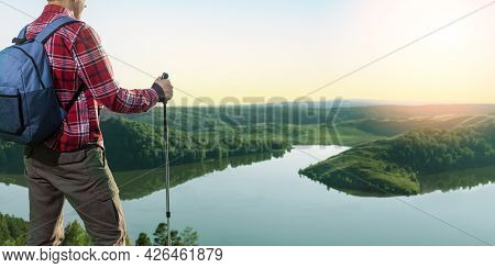 Man Hiker Standing On A Ledge Of A Mountain, Enjoying The Beautiful Sunset. Hiking, Freedom Outdoor
