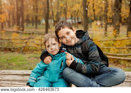 Little Brother With Brother Sit At The Outdoor. Fraternal Relations. Two Happy Boys In The Woods. Cu