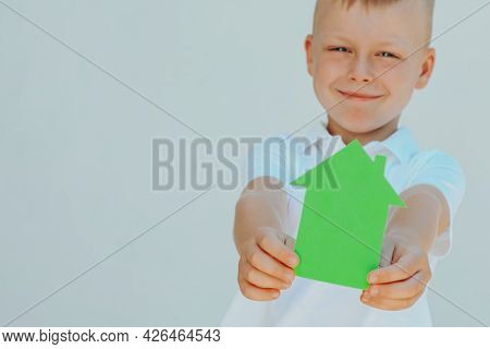 Boy Holding A House Made Of Green Paper Concept Of Ecological Houses. Concept Of Ecological Houses