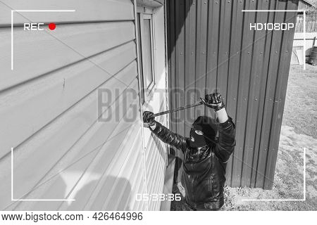Cctv View Of Burglar Breaking In To Home Through Window With Crowbar. Protection Of A Private Reside