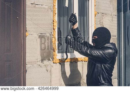 Burglar With Obscured Face Trying To Break The Window. A Masked Man Breaks A Window With A Crowbar.
