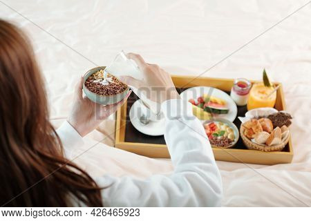 Young Woman Sitting In Bed And Pouring Fresh Milk In Bowl With Muesli When Eating Breakfast In Bed