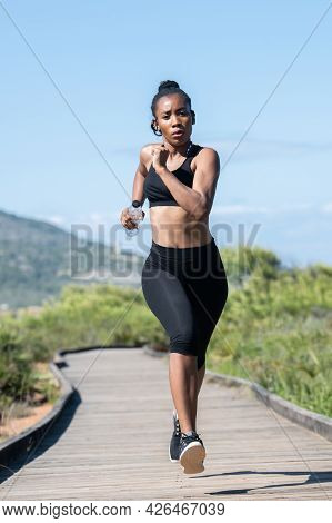 Vigorous Afro American Woman Running Along A Wooden Runway: Exercise And Lifestyle Concept.