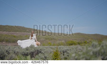Young Woman Runs Beautifully In White Dress In Field. Action. Feeling Of Lightness And Freedom In Wo