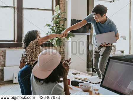 Colleagues doing a fist bump in the office