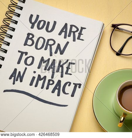 You are born to make an impact - inspiration handwriting in a spiral note with a cup of coffee, make a difference concept