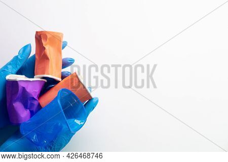 Ecological Impact. Earth Care. Save Environment. Hands In Medical Gloves Holding Colorful Plastic Li