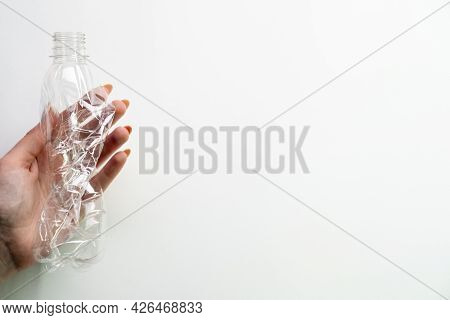 Garbage Reduction. Zero Waste. Green Peace Poster. Female Hand Holding Used Crushed Plastic Bottle I