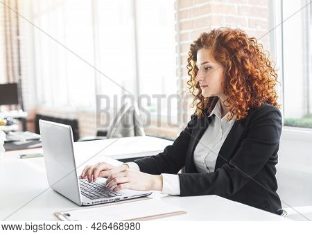 Beautiful Young Red-haired Woman In A Business Suit Works In An Office With A Laptop