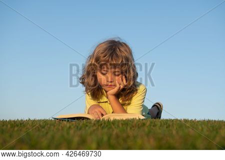 Clever Child Boy Reading Book Laying On Grass On Grass And Sky Background With Copy Space. Kids Imag