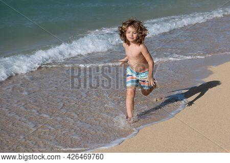 Kid Running On Beach. Happy Child Run In Sea On Summer Vacation. Travel And Adventure On Sea Or Ocea