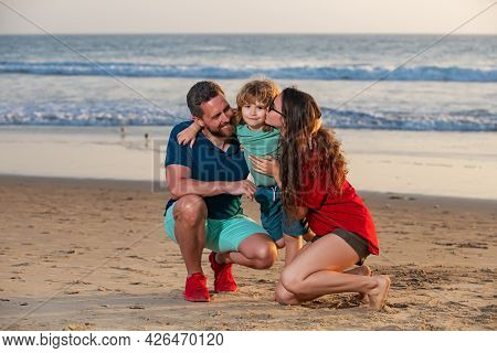 Family Walking To The Beach On A Sunny Day. Sea Vacation. Parents And Children Hugging At Ocean Shor