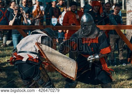 Imitation Of Jousting In The Arena. Two Representatives Of Historical Clubs In Armor Fight With Swor