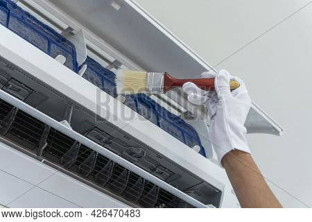 Cleaning Dirty Air Filter Inside Air Conditioners. With Dust Brush