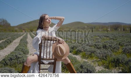 Young Woman Is Sitting On Chair In Field. Action. Beautiful Woman In White Dress Poses With Chair In